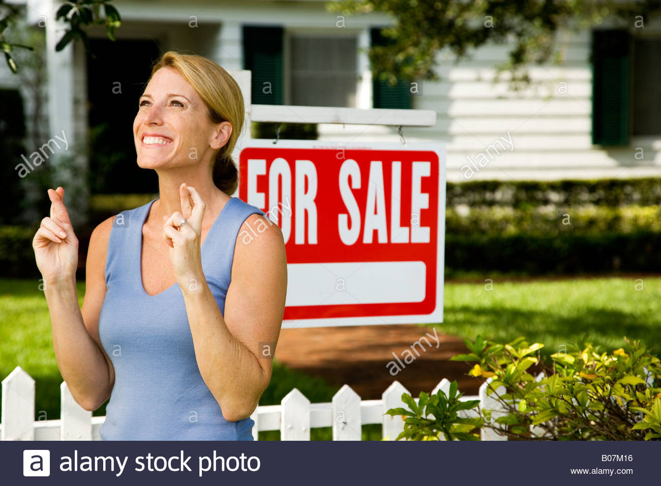 Woman standing by a for sale sign outside a family house, fingers crossed - Stock Image