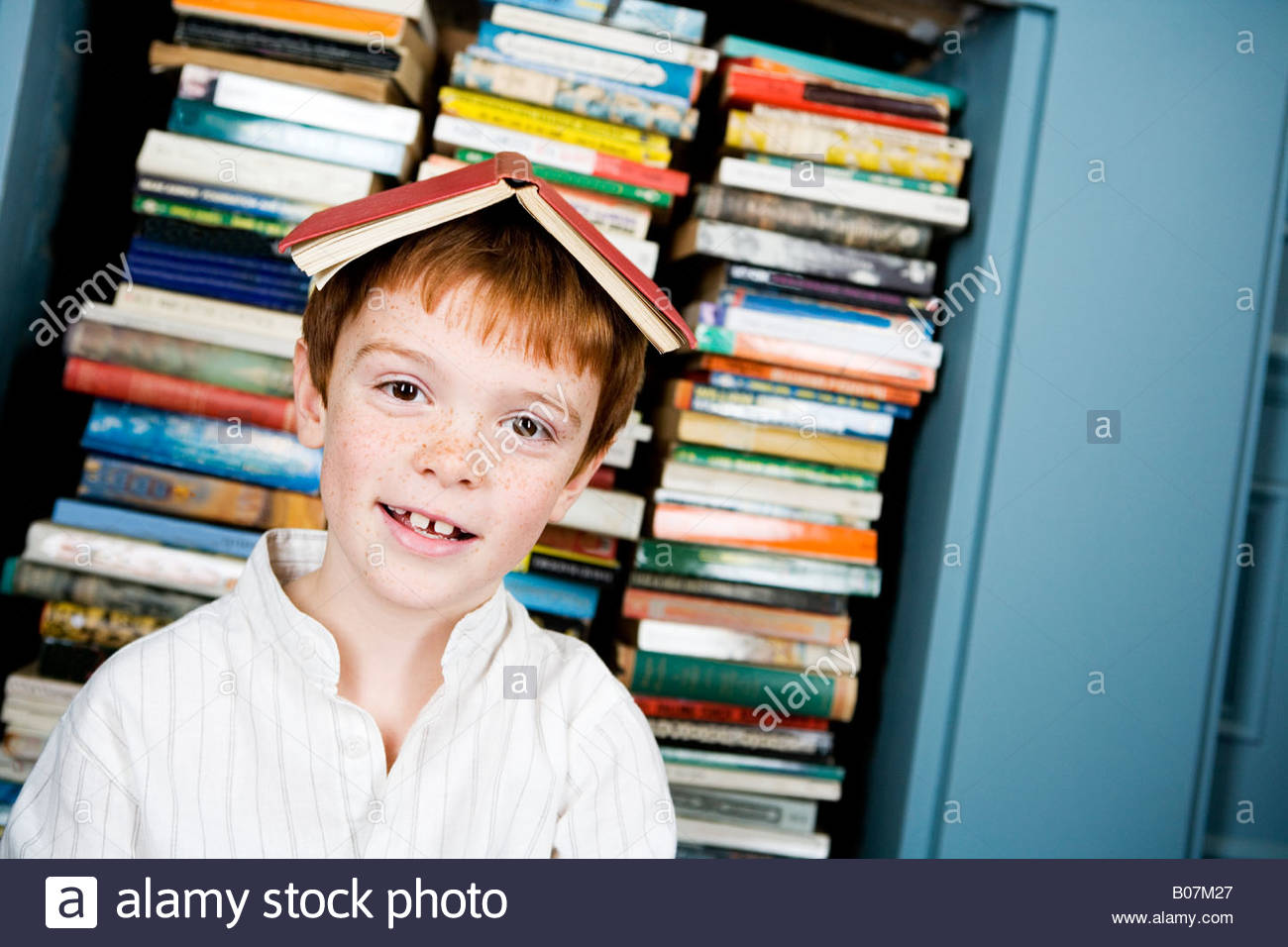 young ginger haired boy with book on his head Stock Photo