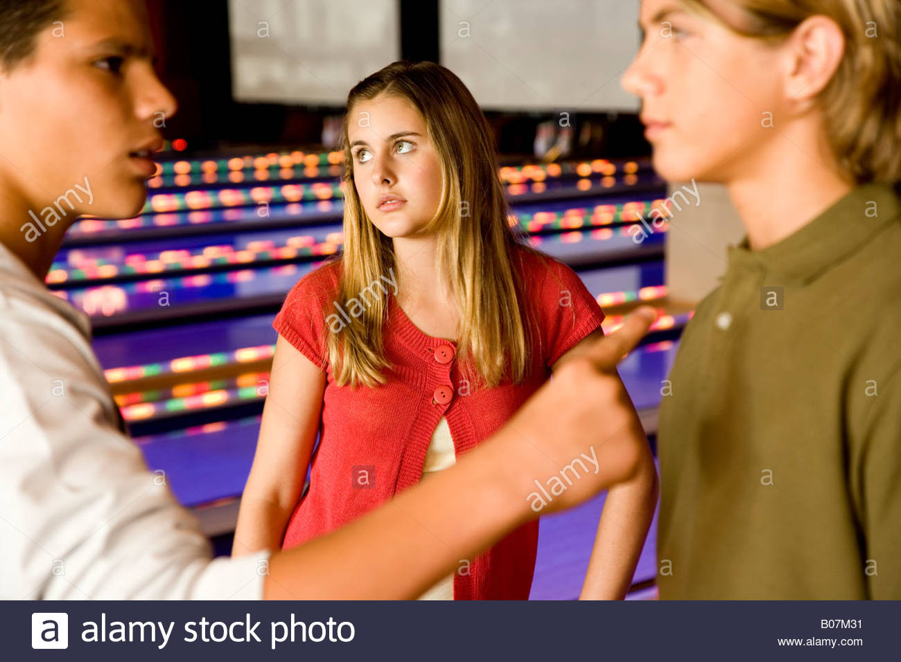 Two teenage boys in a bowling alley having an argument whilst a girl looks fed up with them - Stock Image