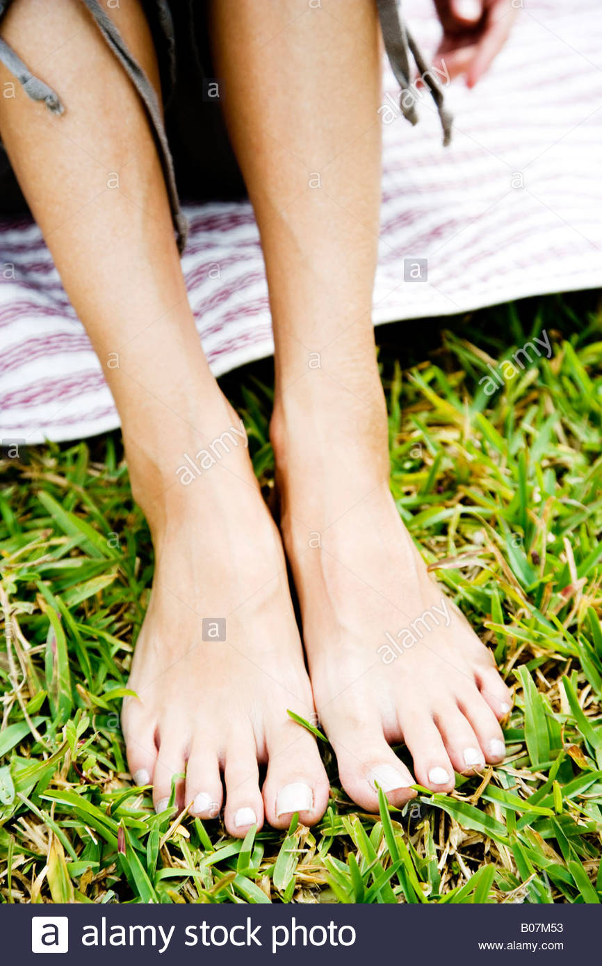 woman's bare feet on the grass - Stock Image