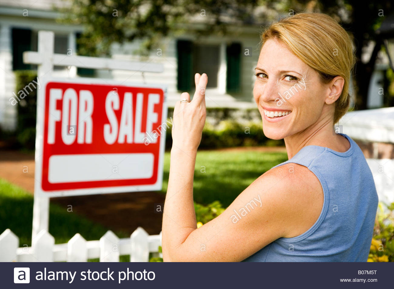 Woman standing by a for sale sign outside a family house, fingers crossed Stock Photo