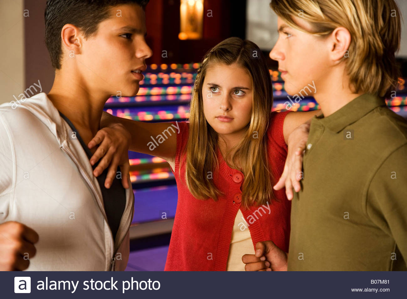 Argument between teenage boys in a bowling alley, girl mediating between them - Stock Image