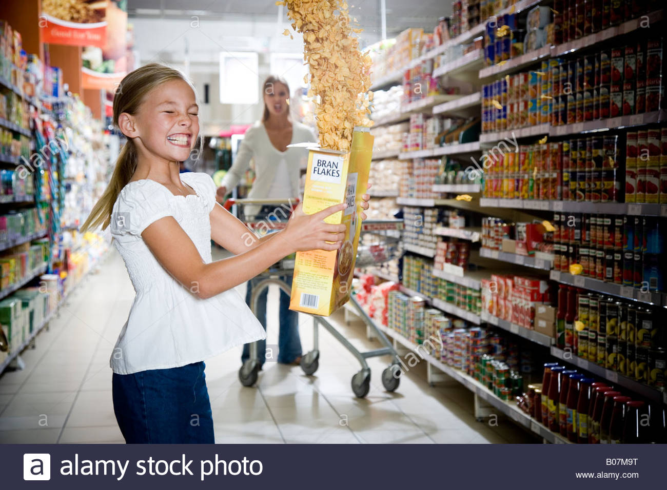 Naughty young girl emptying cereal packet in a supermarket - Stock Image
