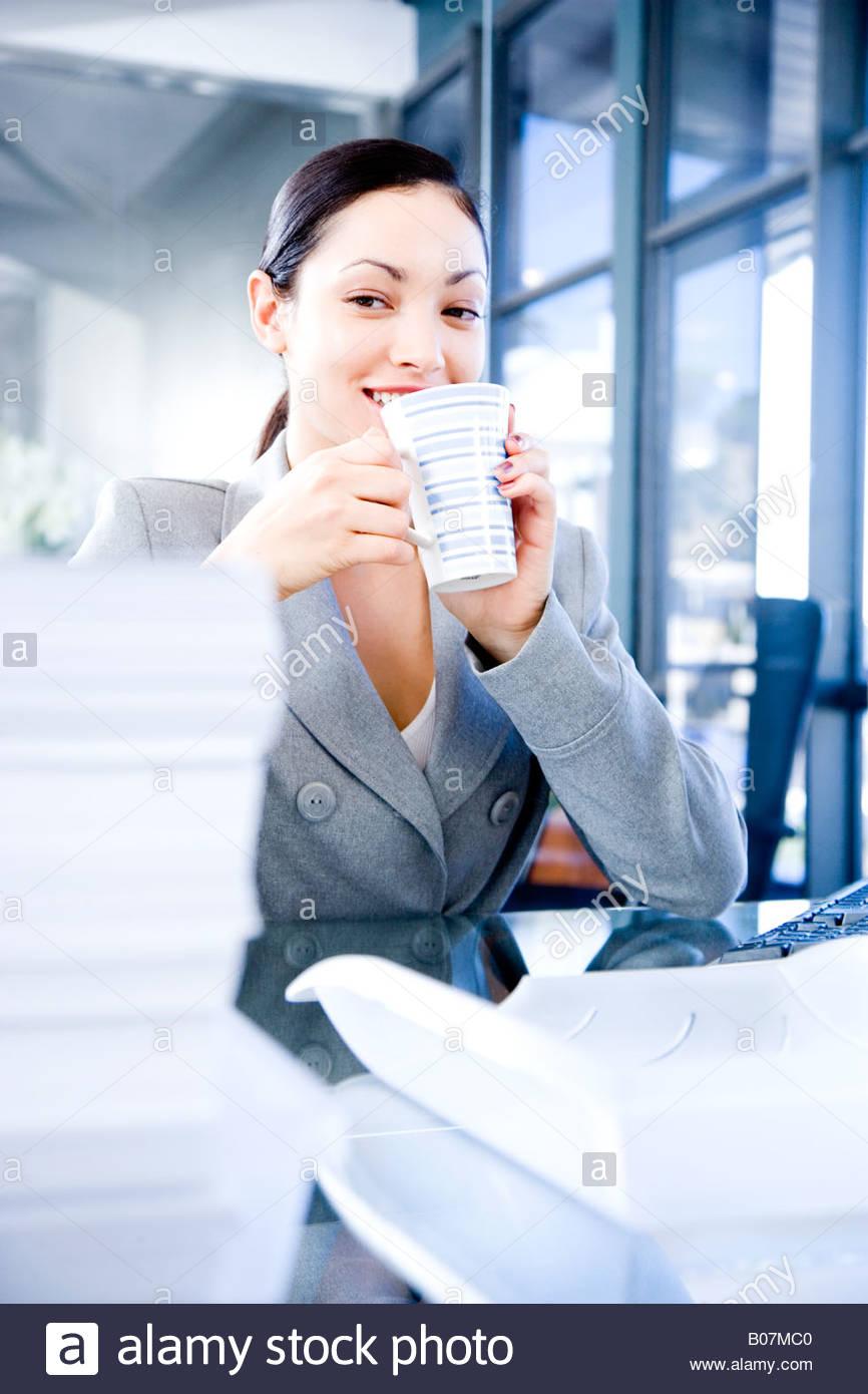 Businesswoman enjoying a coffee or tea break - Stock Image