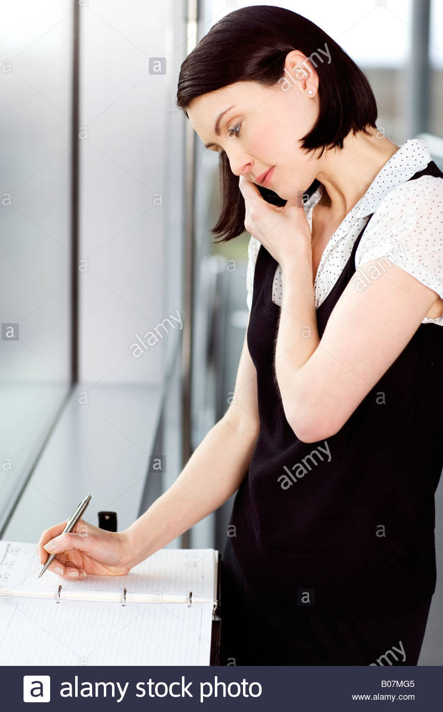 Young businesswoman or secretary making an appointment in a diary - Stock Image