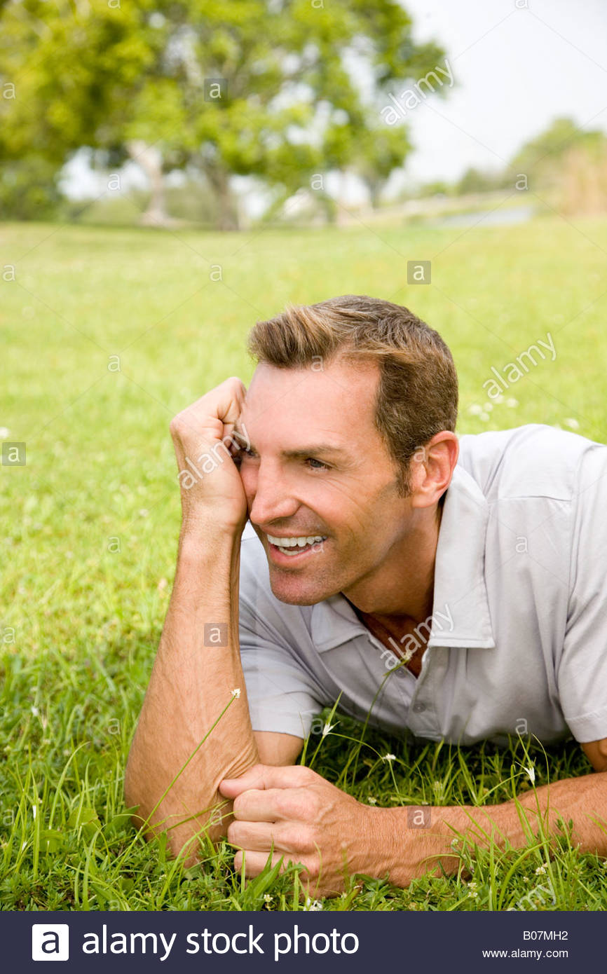 portrait man lying on grass leaning on elbow - Stock Image