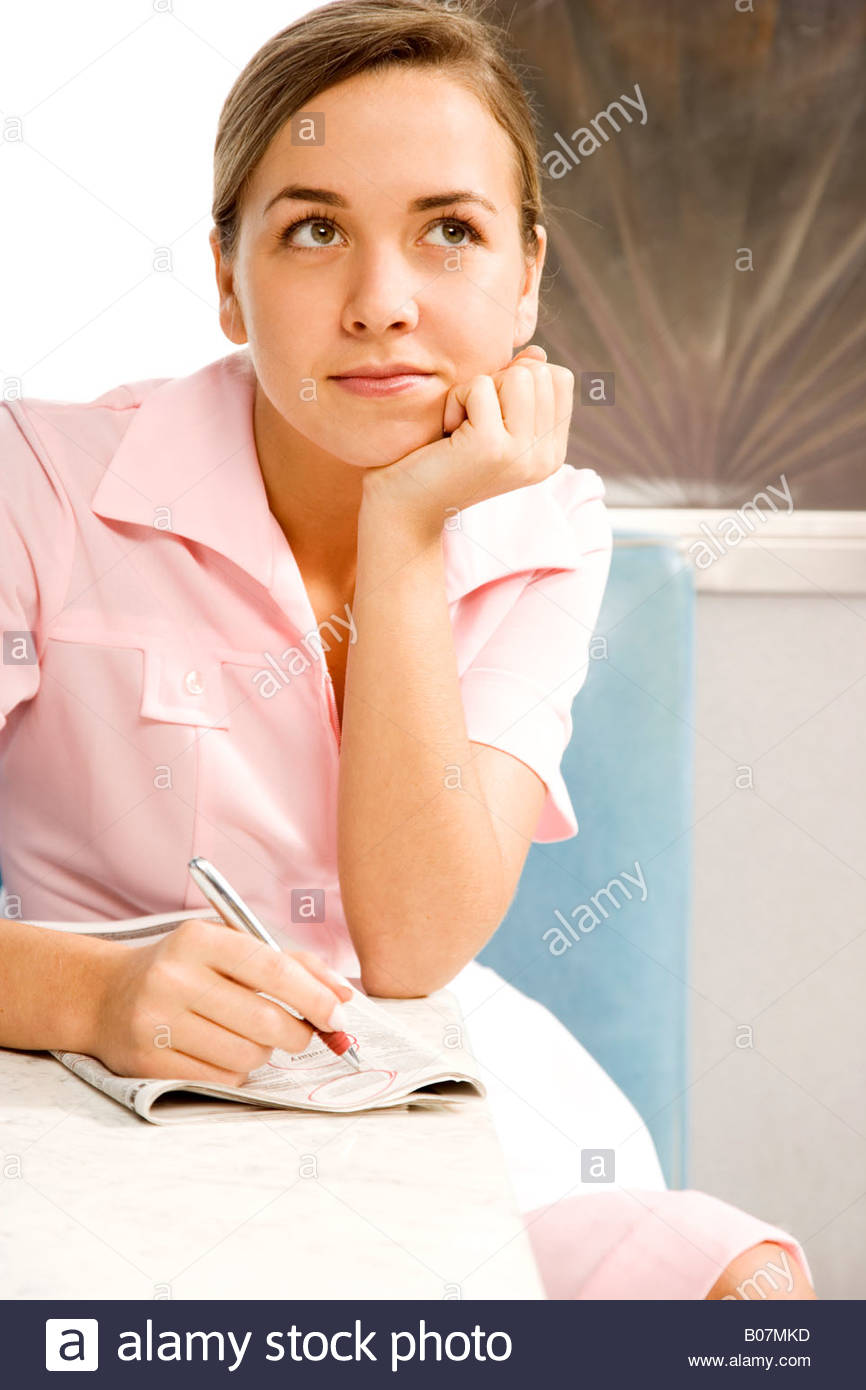 Diner waitress daydreaming whilst looking at the classified section of a newspaper - Stock Image