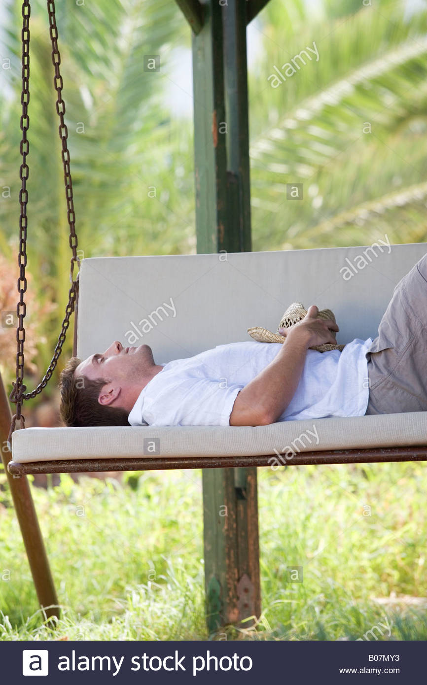 A man snoozing on a swing - Stock Image