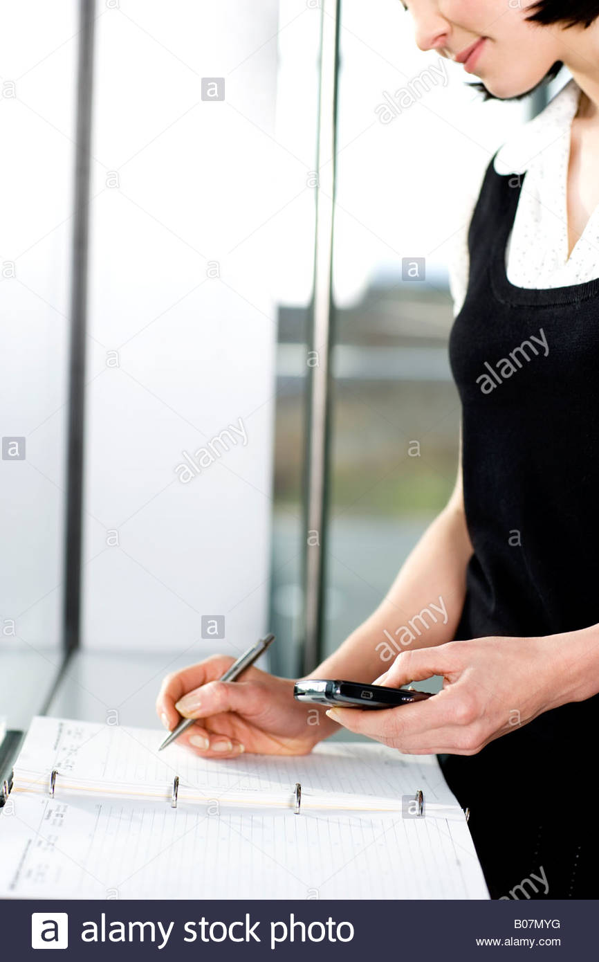 Businesswoman or secretary making an appointment in a diary - Stock Image