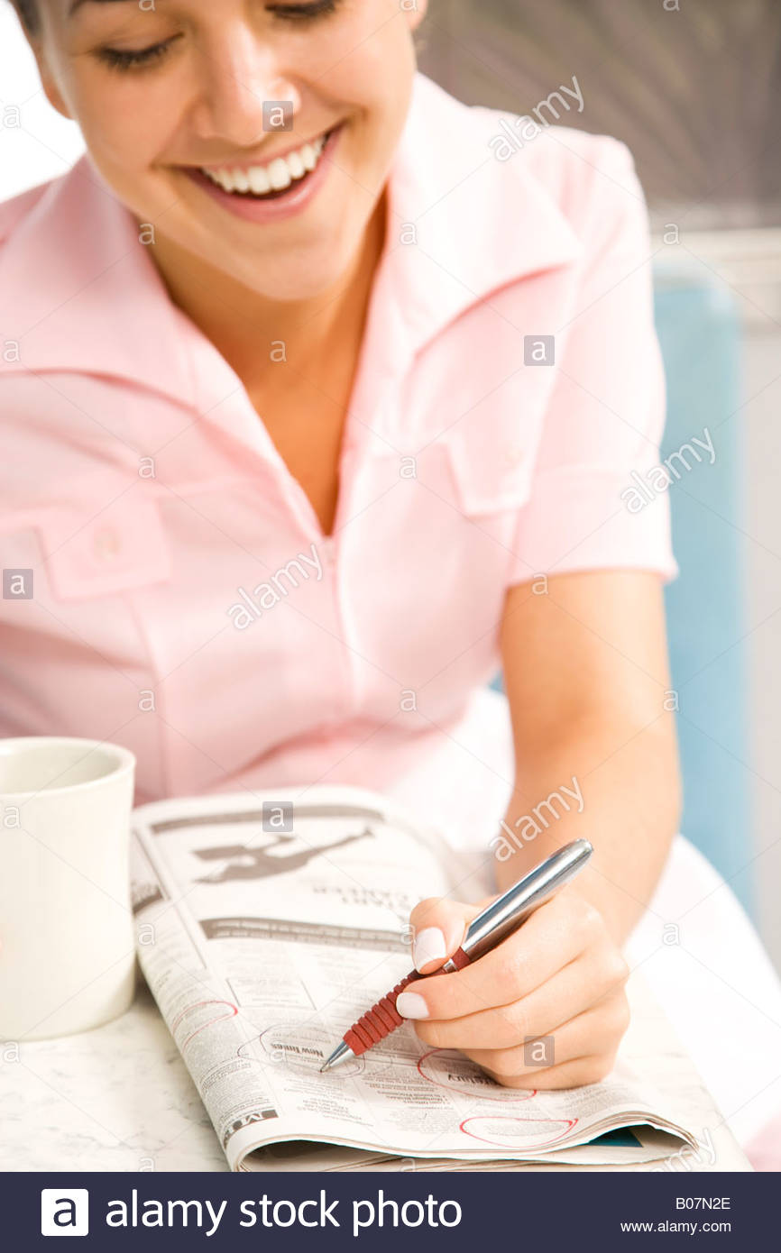 Diner waitress looking at the classified section of a newspaper - Stock Image