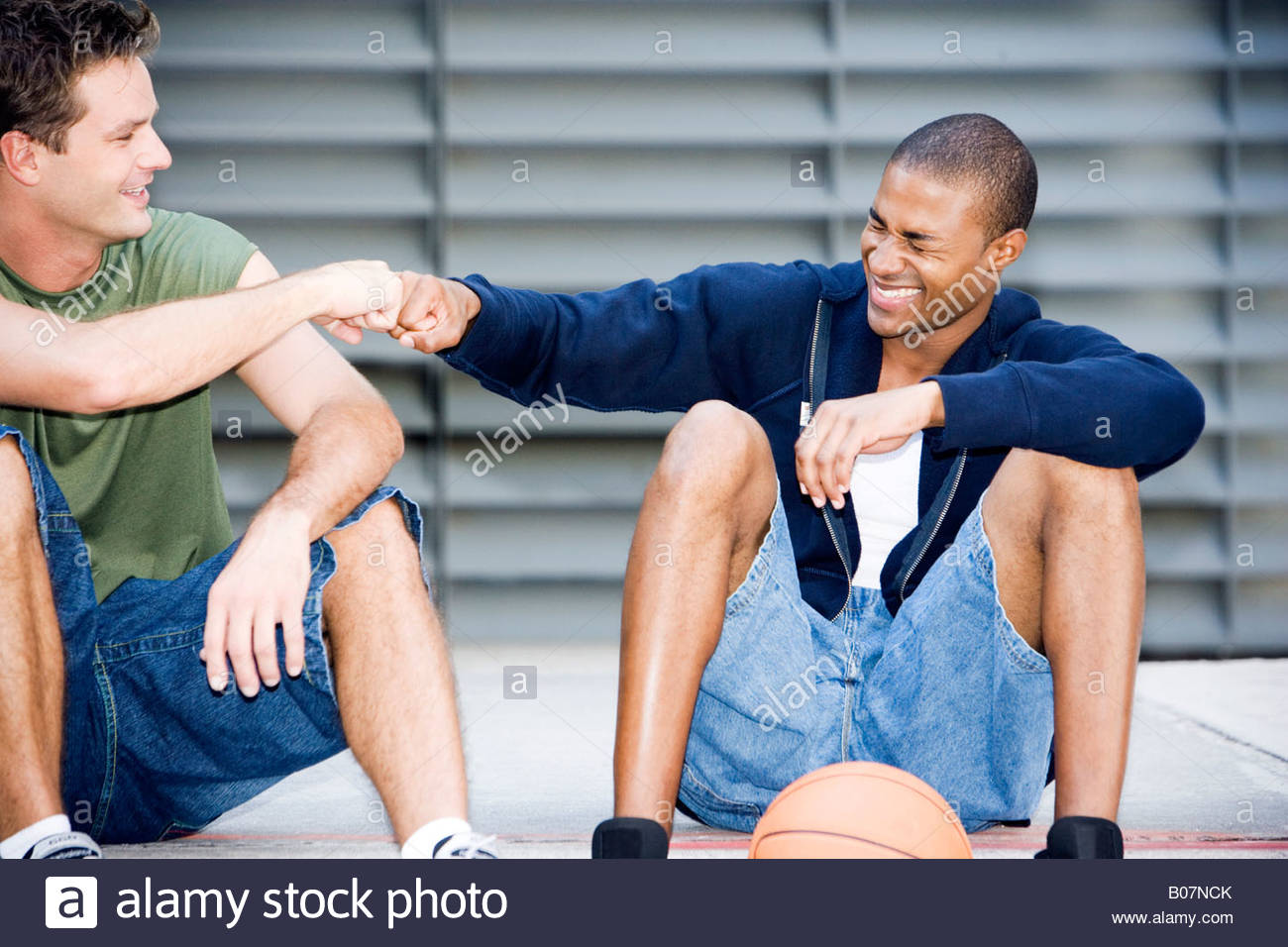 Portrait of a young African American and Caucasian men sitting smiling making greeting hand gestures - Stock Image