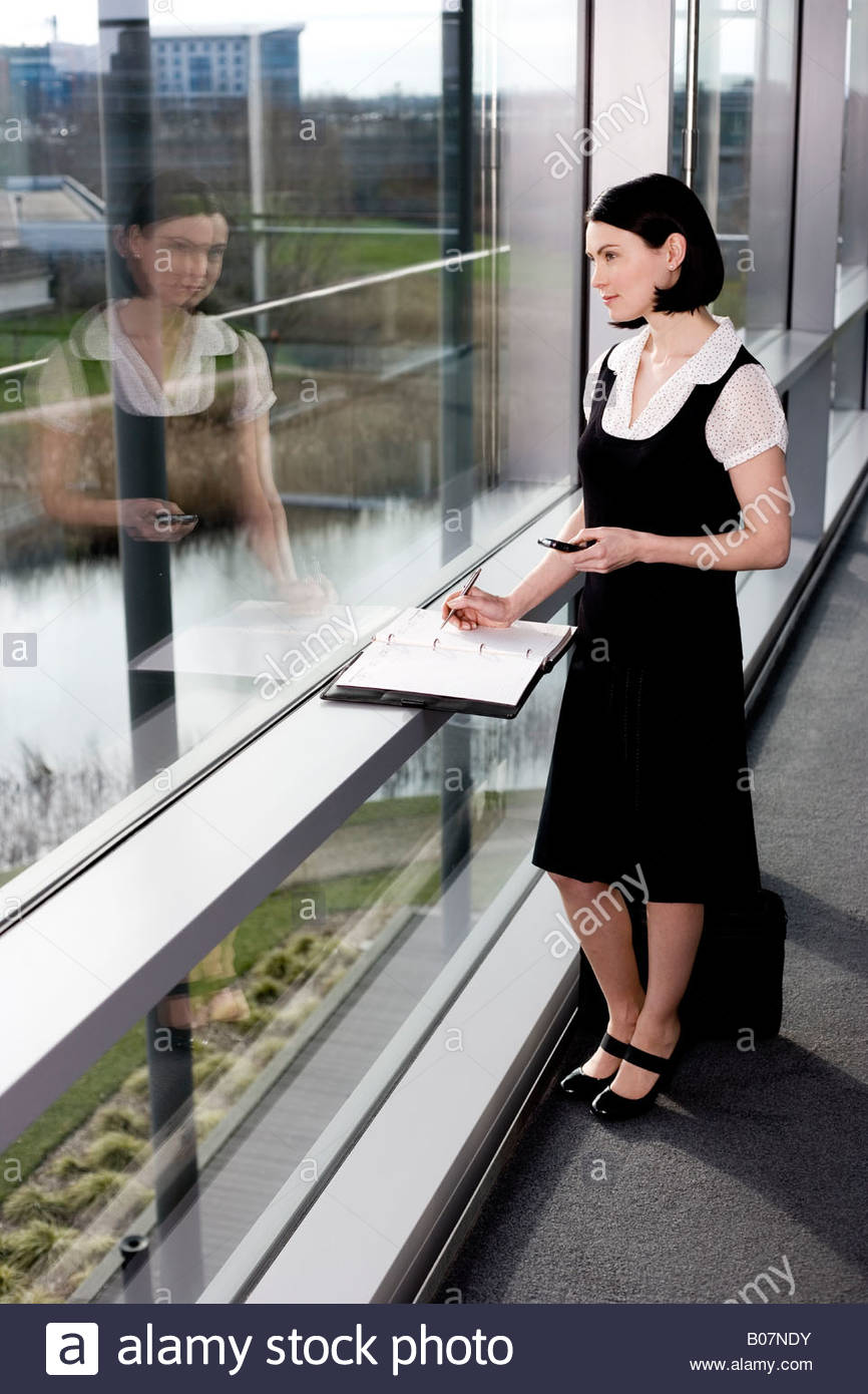 Businesswoman or secretary with an appointments diary, staring out of the window - Stock Image