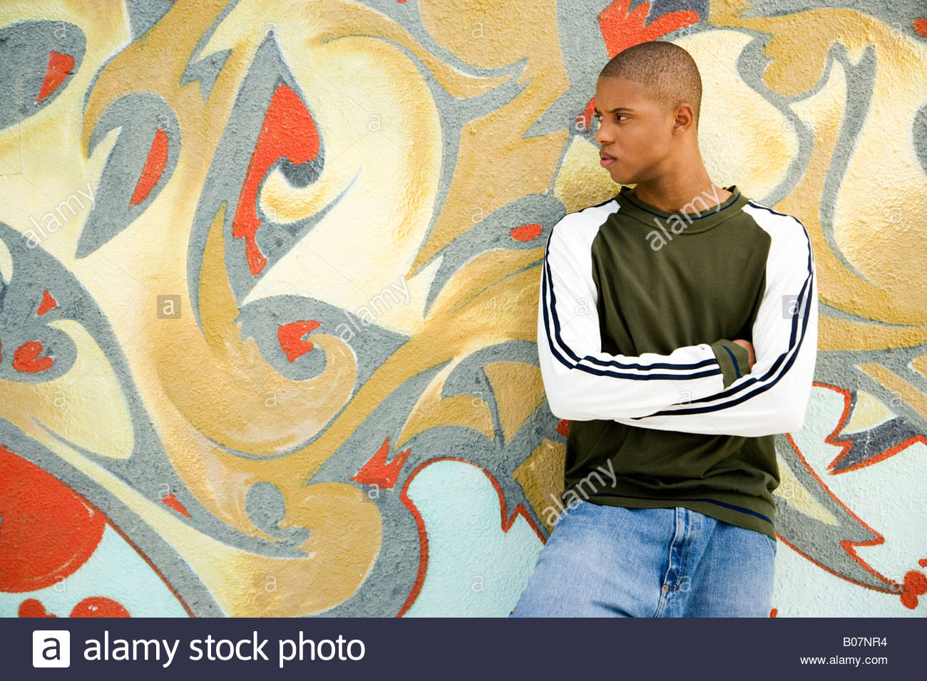 Portrait of a young African American man in front of a graffiti ...