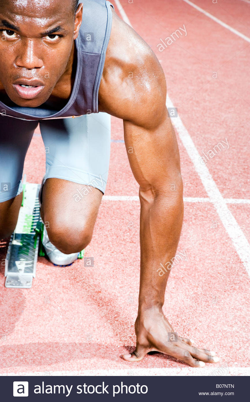Portrait of a male athlete in the starting blocks - Stock Image