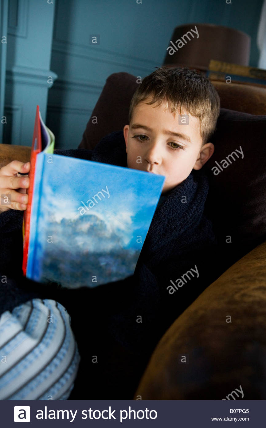 boy reading book in his pajamas - Stock Image