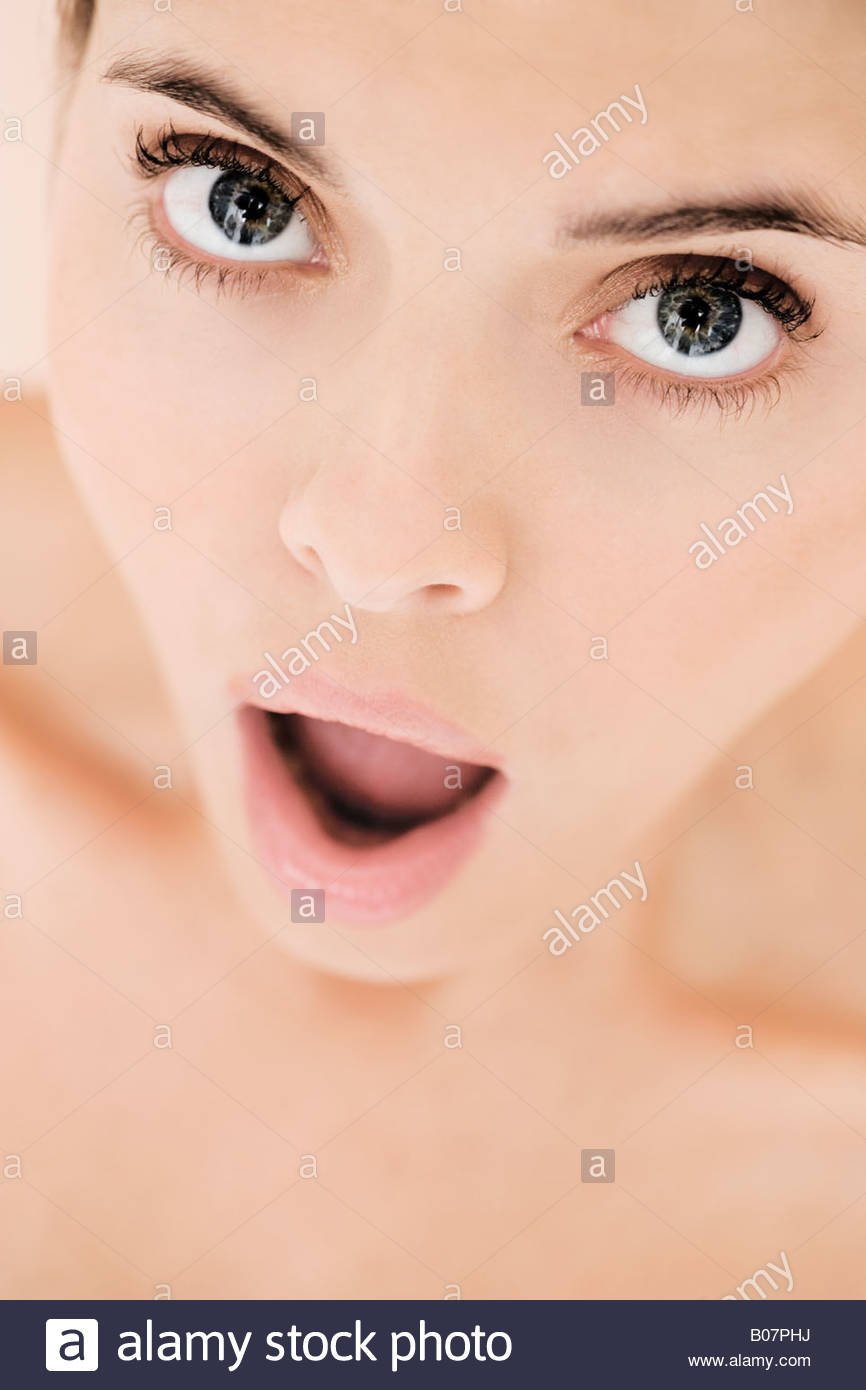 Portrait of young woman with mouth open in shock - Stock Image