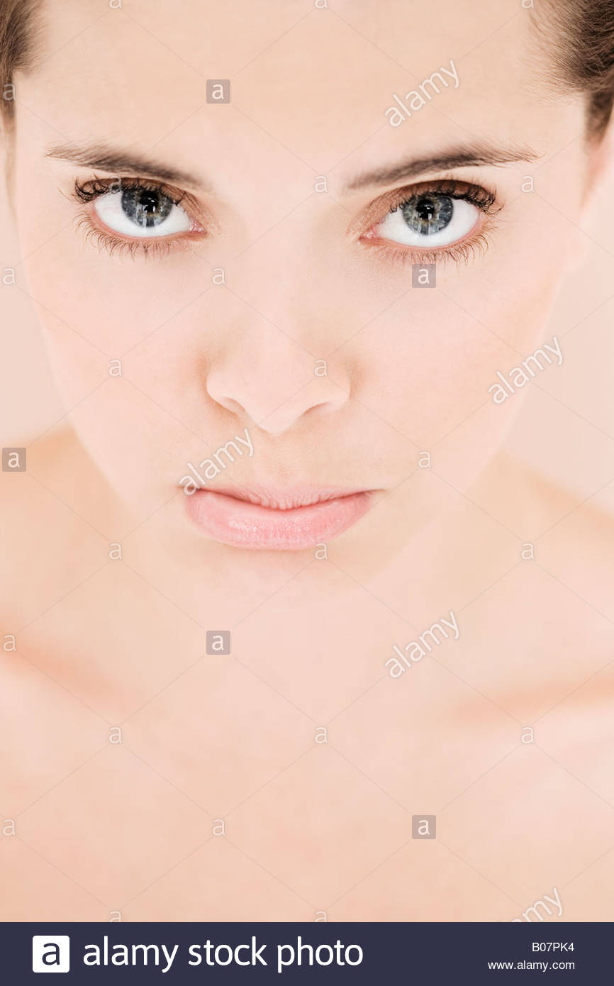 Portrait of young woman looking fed-up - Stock Image