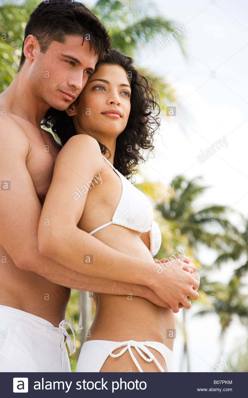 Couple in swimwear on tropical holiday, drinking champagne - Stock Image