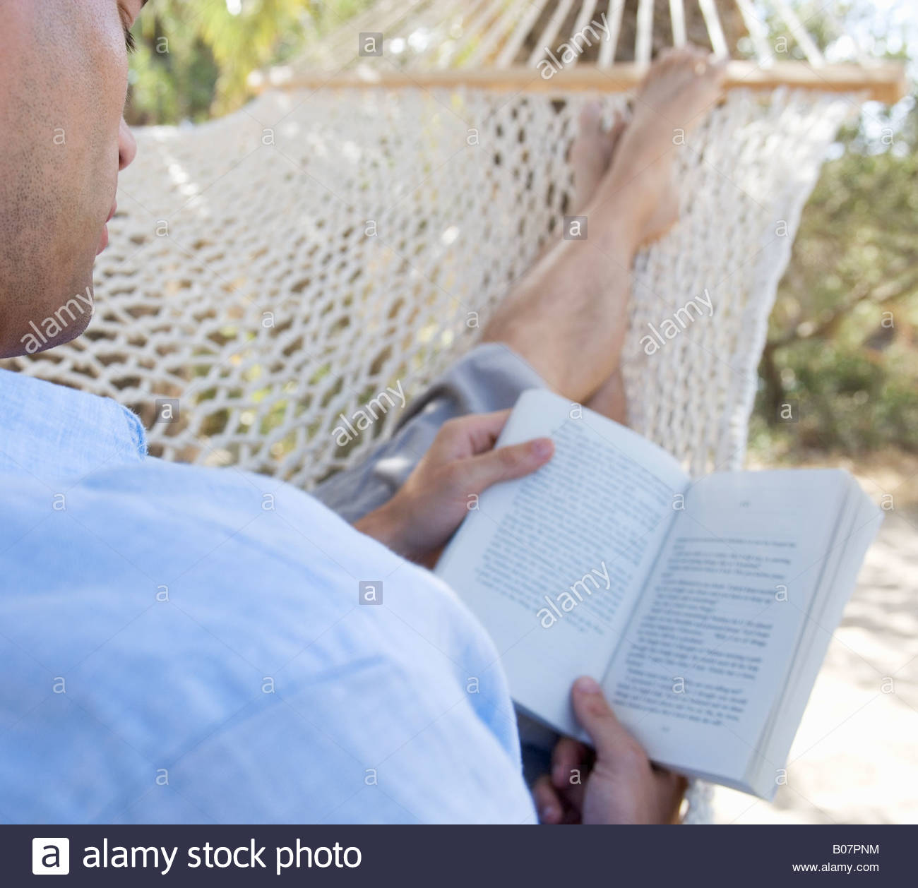 A man relaxing in a hammock - Stock Image