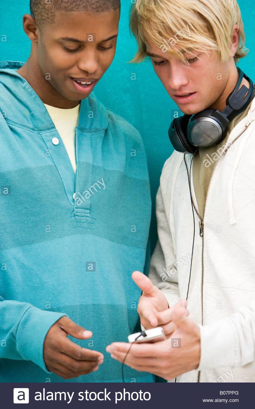 Two young men looking at an MP3 Player leaning against a green painted wall - Stock Image