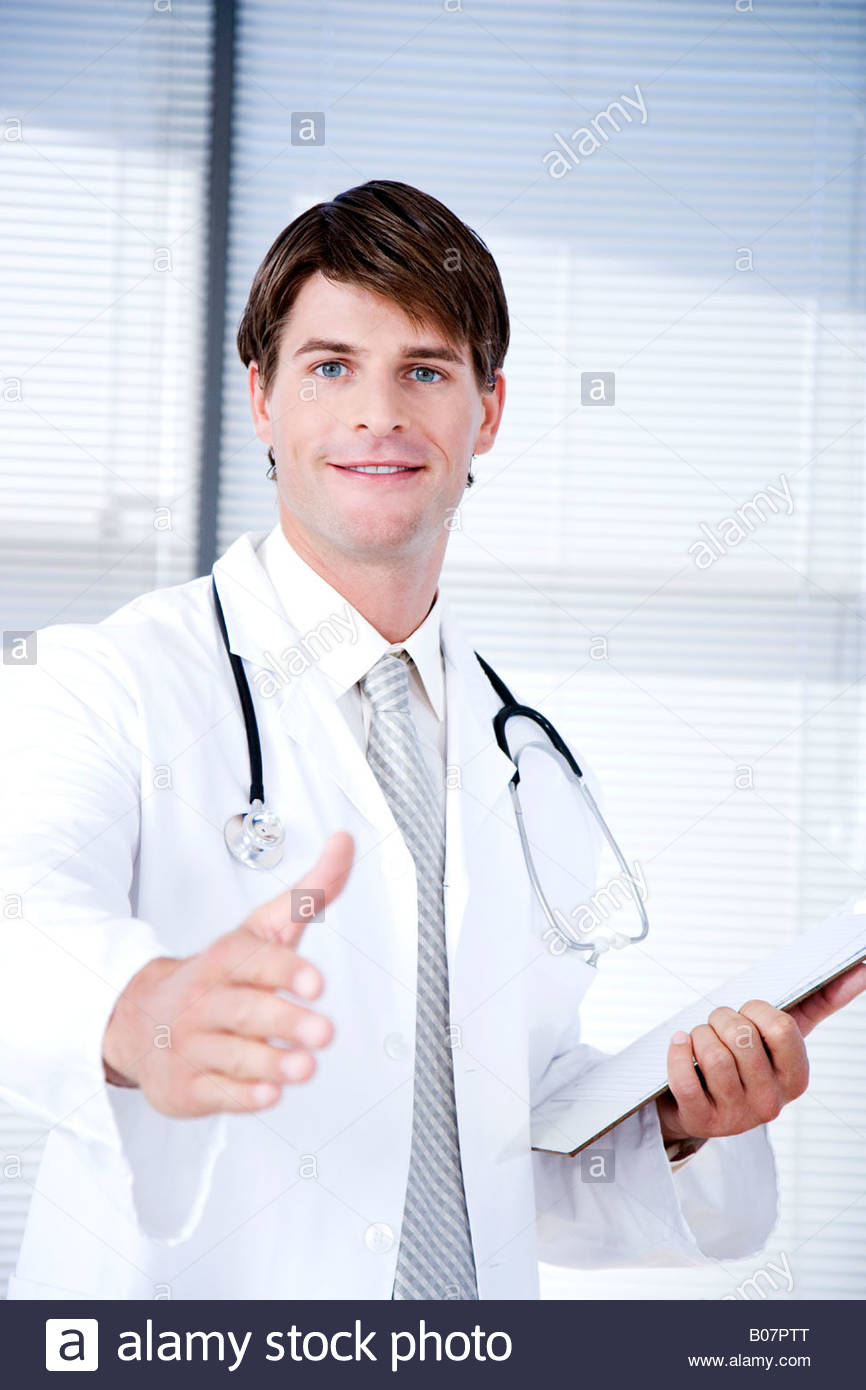 Male doctor with his hand out for  handshake - Stock Image