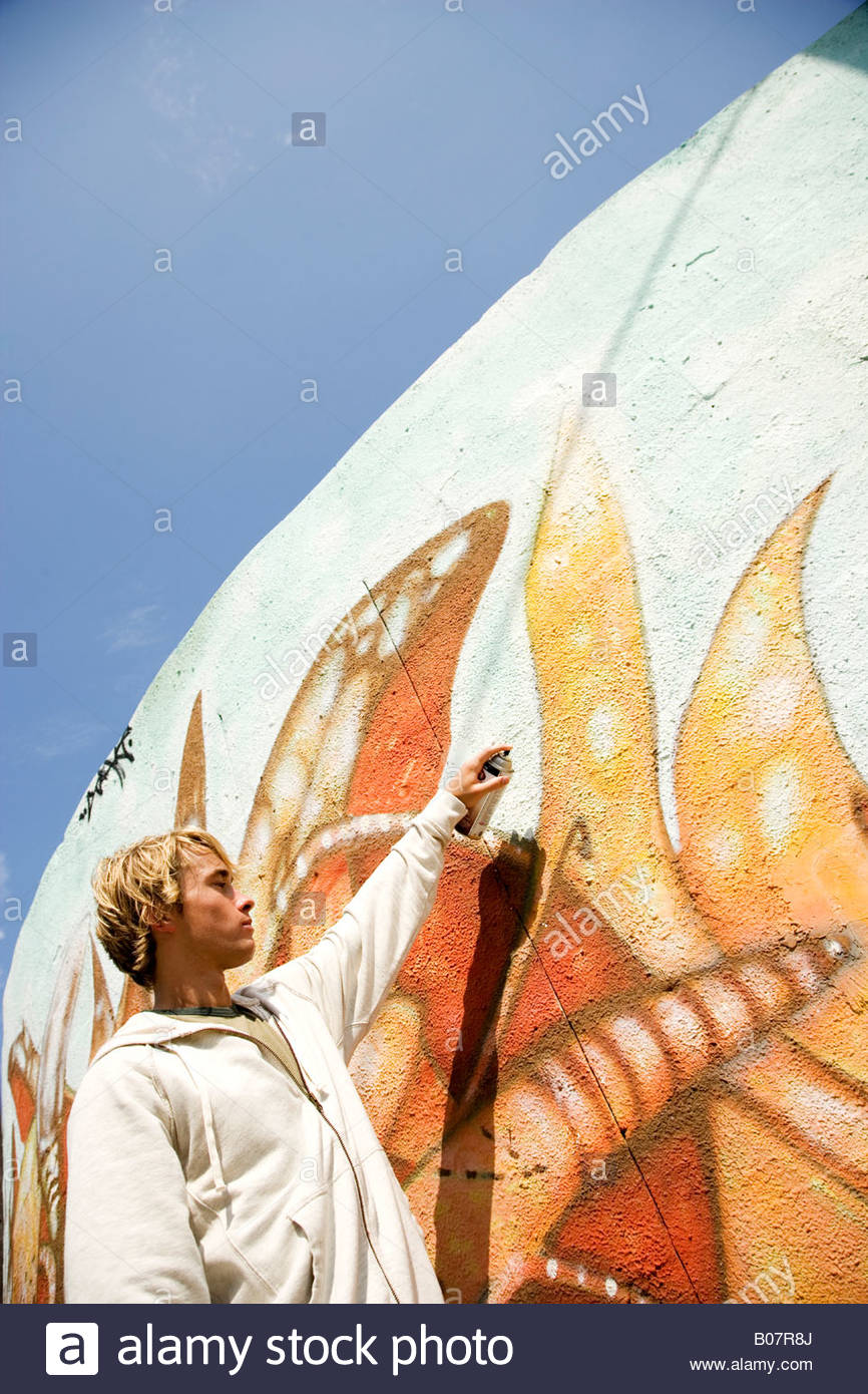 Portrait of a young man vandalizing a wall with graffiti - Stock Image