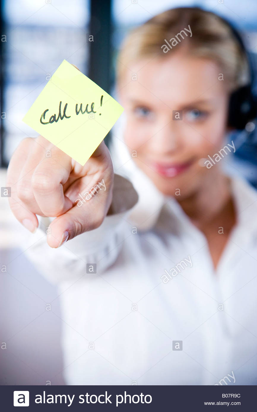 Businesswoman in a call centre with a sticky note saying Call Me - Stock Image
