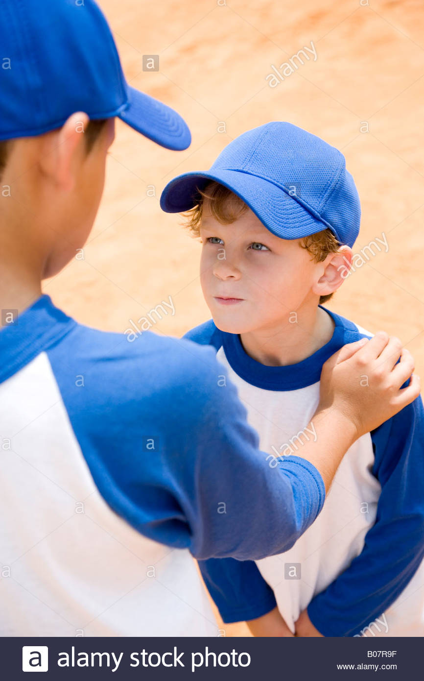 older boy talking down to younger boy at baseball practice - Stock Image