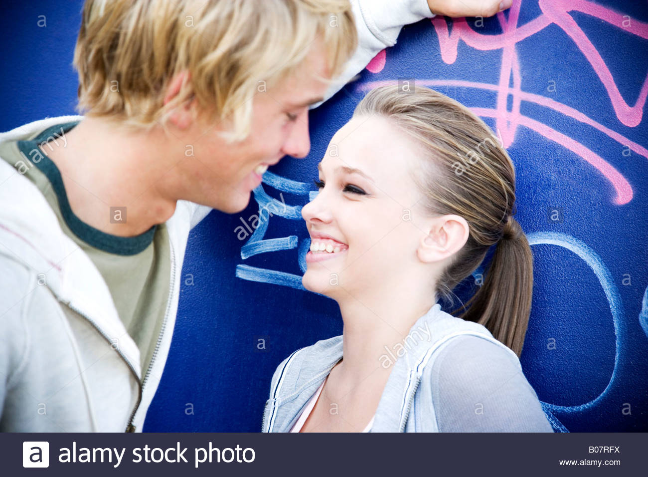 Young teenage couple in front of a graffiti covered wall - Stock Image