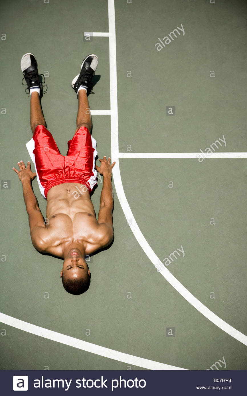 Man laying down on an outdoor basketball court - Stock Image