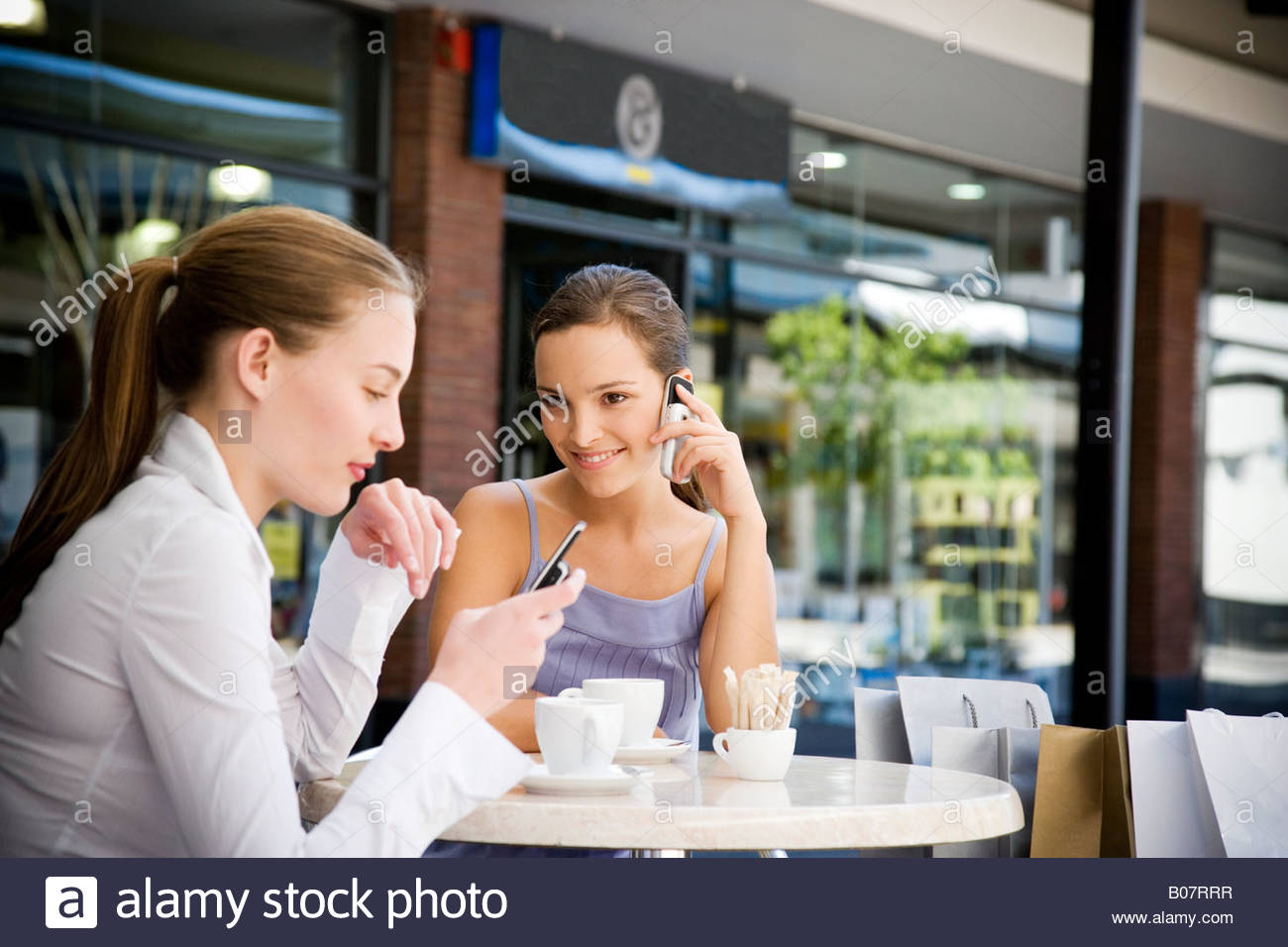 Two women on their mobile phones at a pavement cafe - Stock Image
