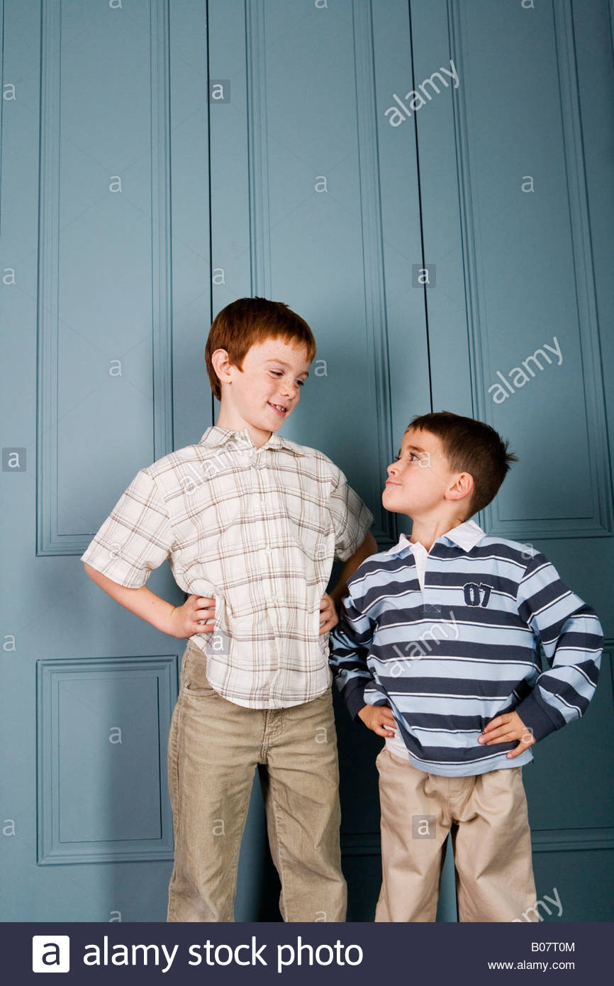 Younger boy staring up at older boy - Stock Image