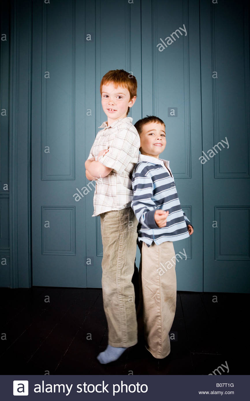 Older and younger boy standing back to back - Stock Image