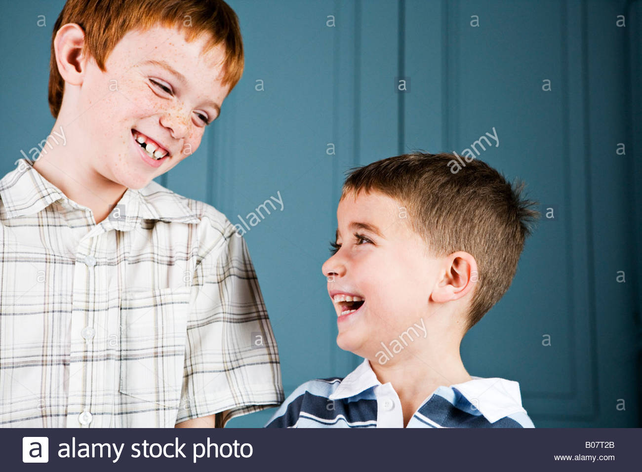 Older and younger boy laughing together - Stock Image