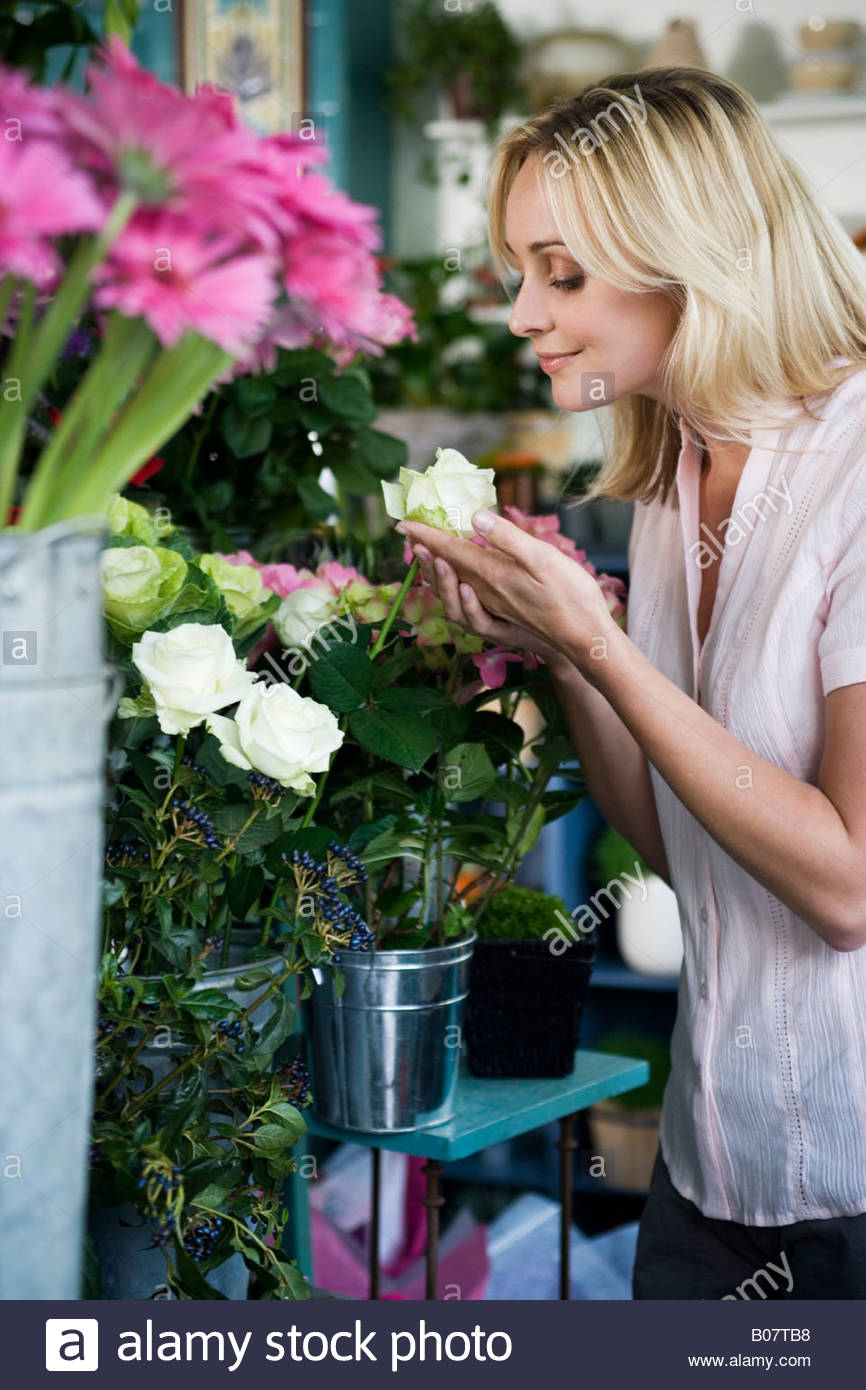 Woman in a florist's shop, smelling a white rose Stock Photo
