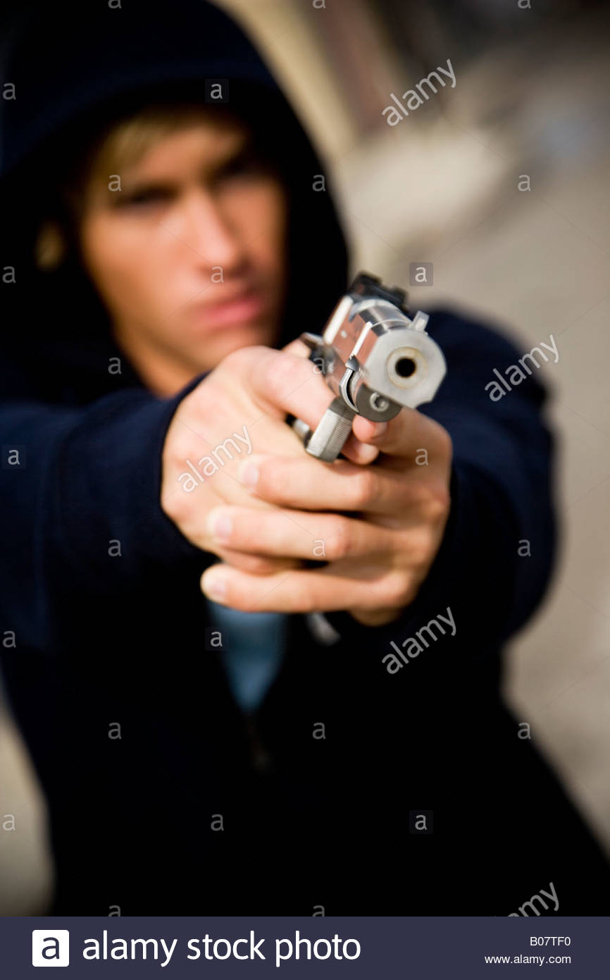 Portrait of a young man holding a gun Stock Photo