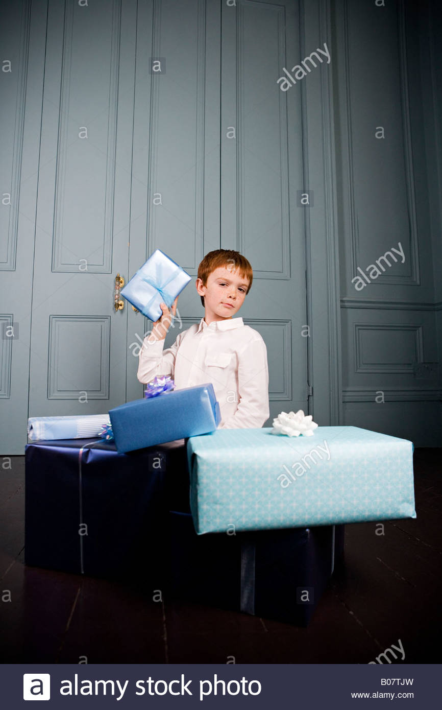 boy shaking present to guess what's inside - Stock Image