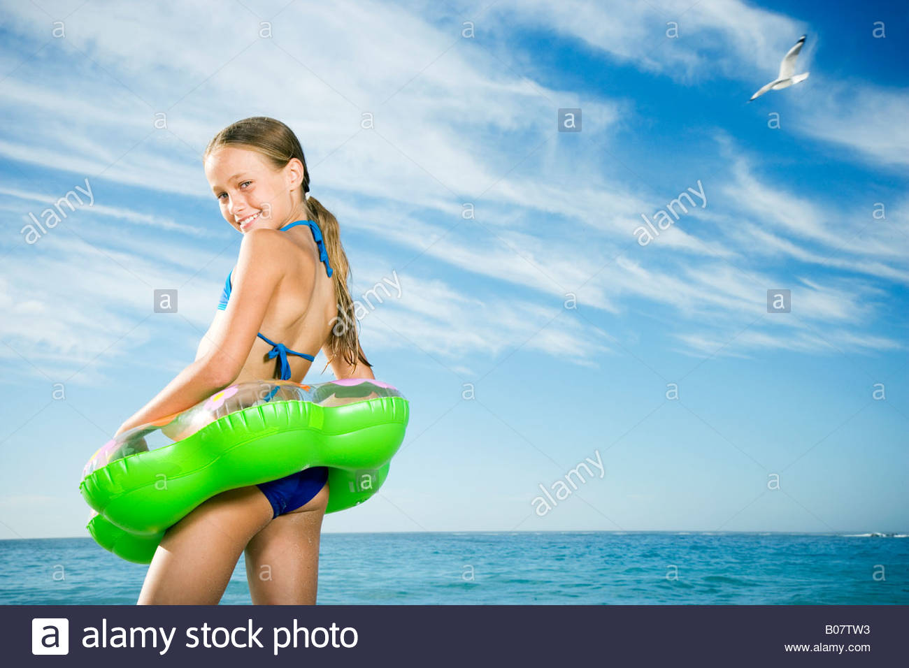 A young girl on the beach with rubber ring Stock Photo