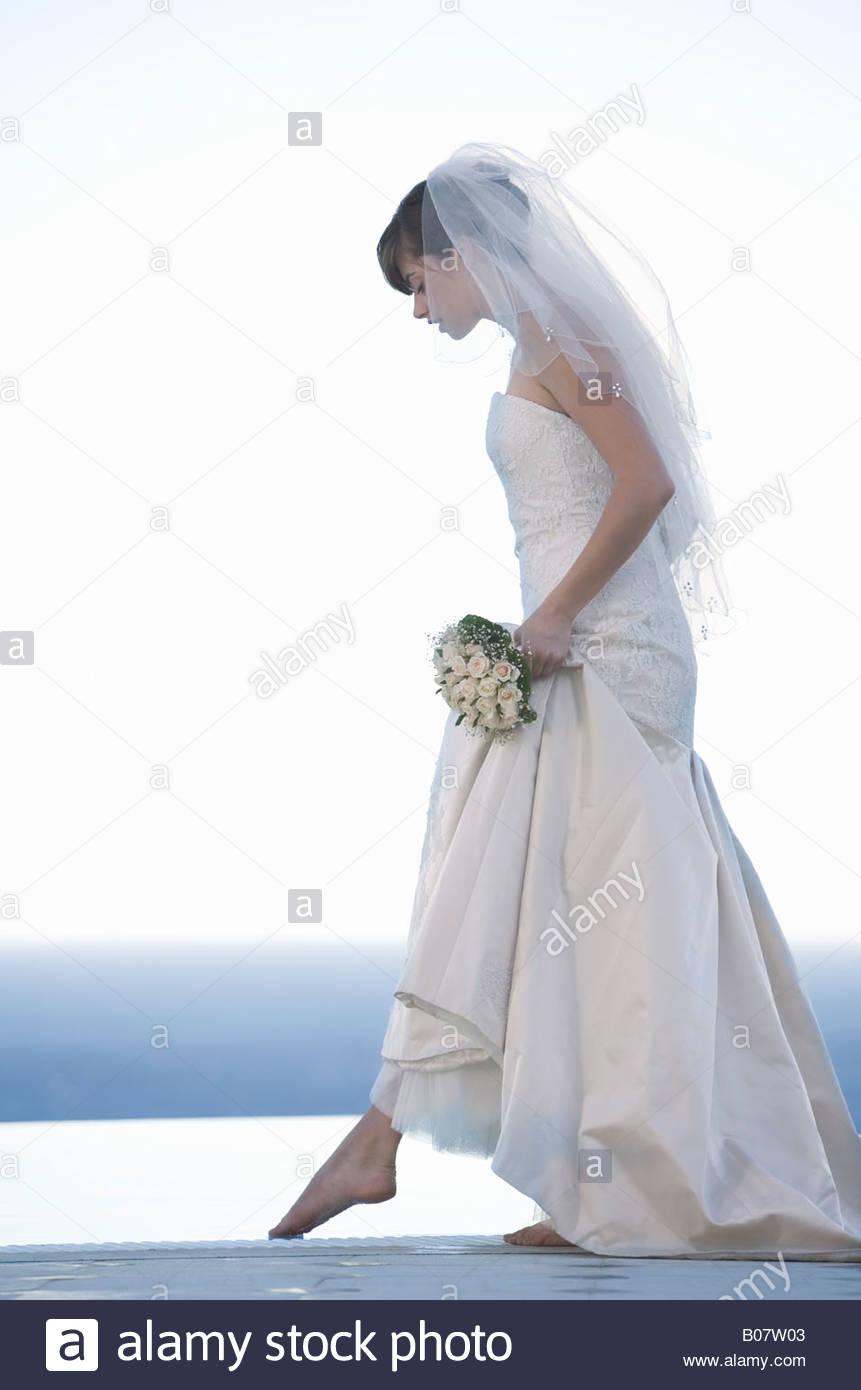 A bride walking barefoot - Stock Image