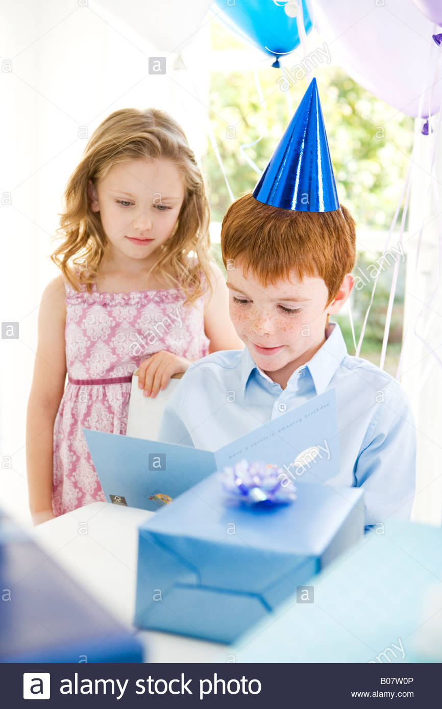 boy reading birthday card at his party - Stock Image