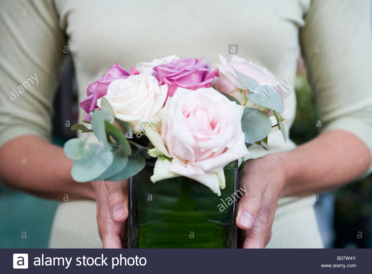 Woman holding a square vase of pink roses - Stock Image
