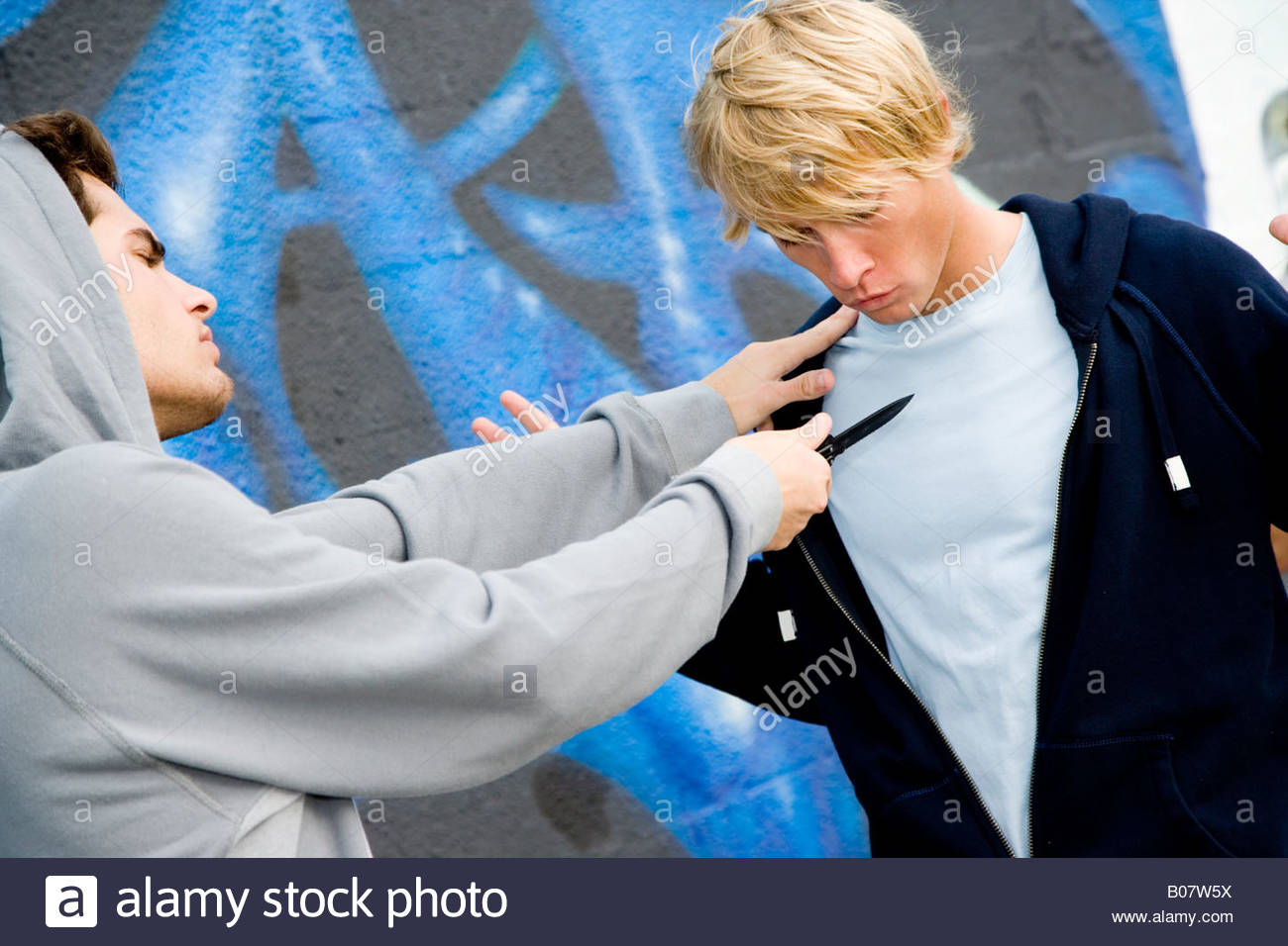 Confrontation between two young men and a group of friends in front of a graffiti covered wall Stock Photo