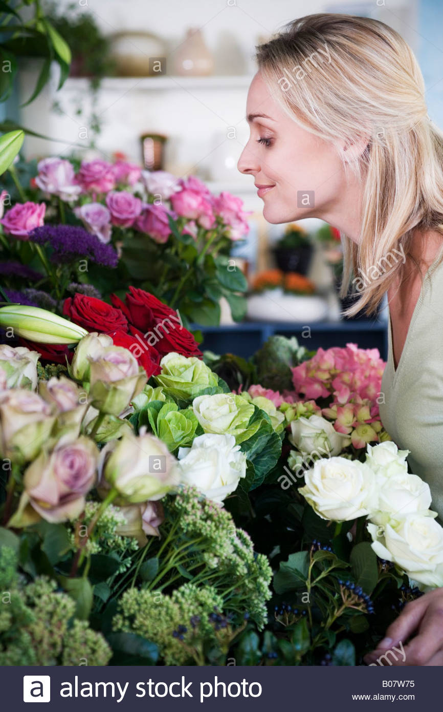 Woman choosing flowers in a florist's shop - Stock Image