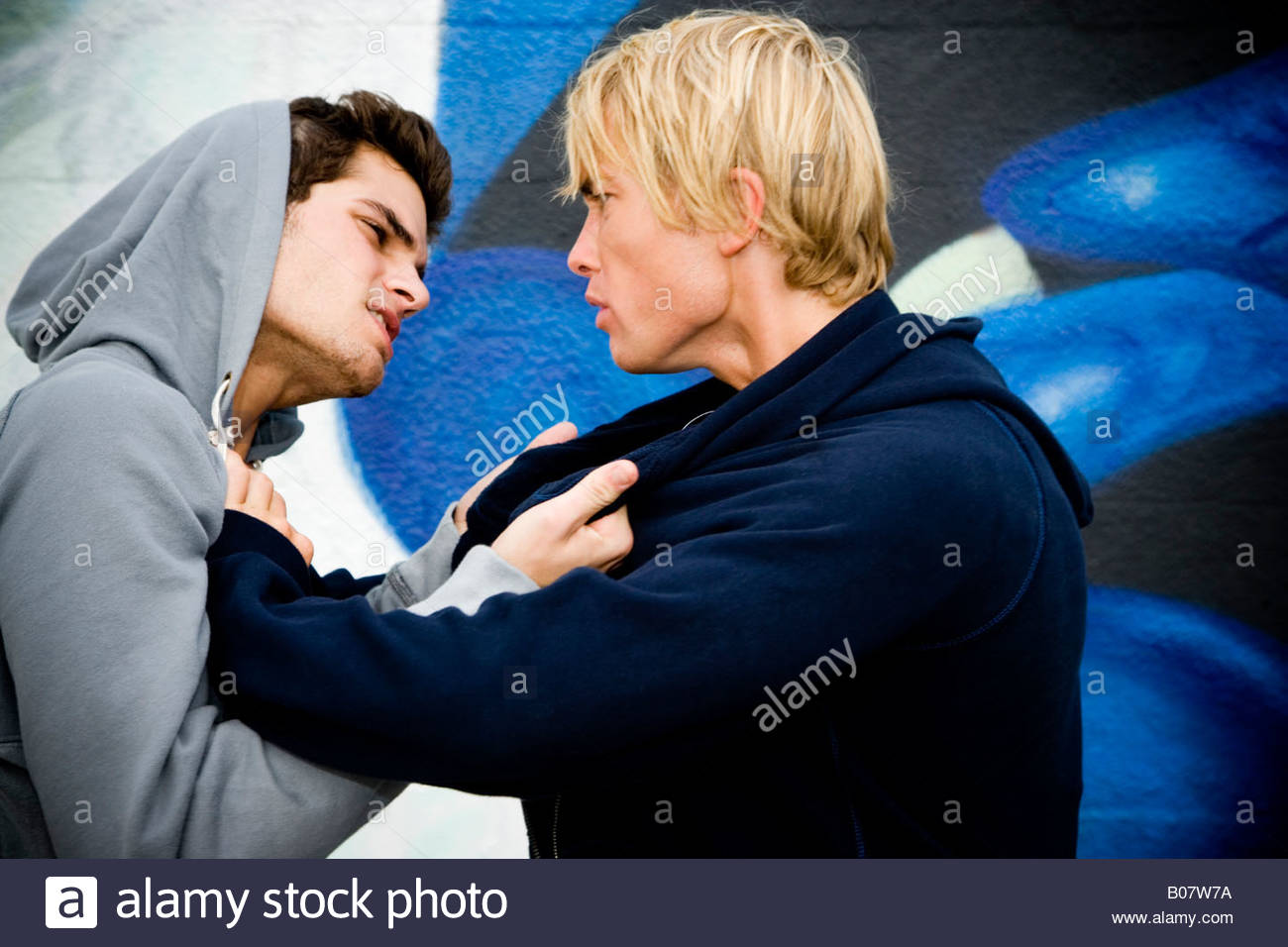 Two men fighting in front of a graffiti covered wall - Stock Image