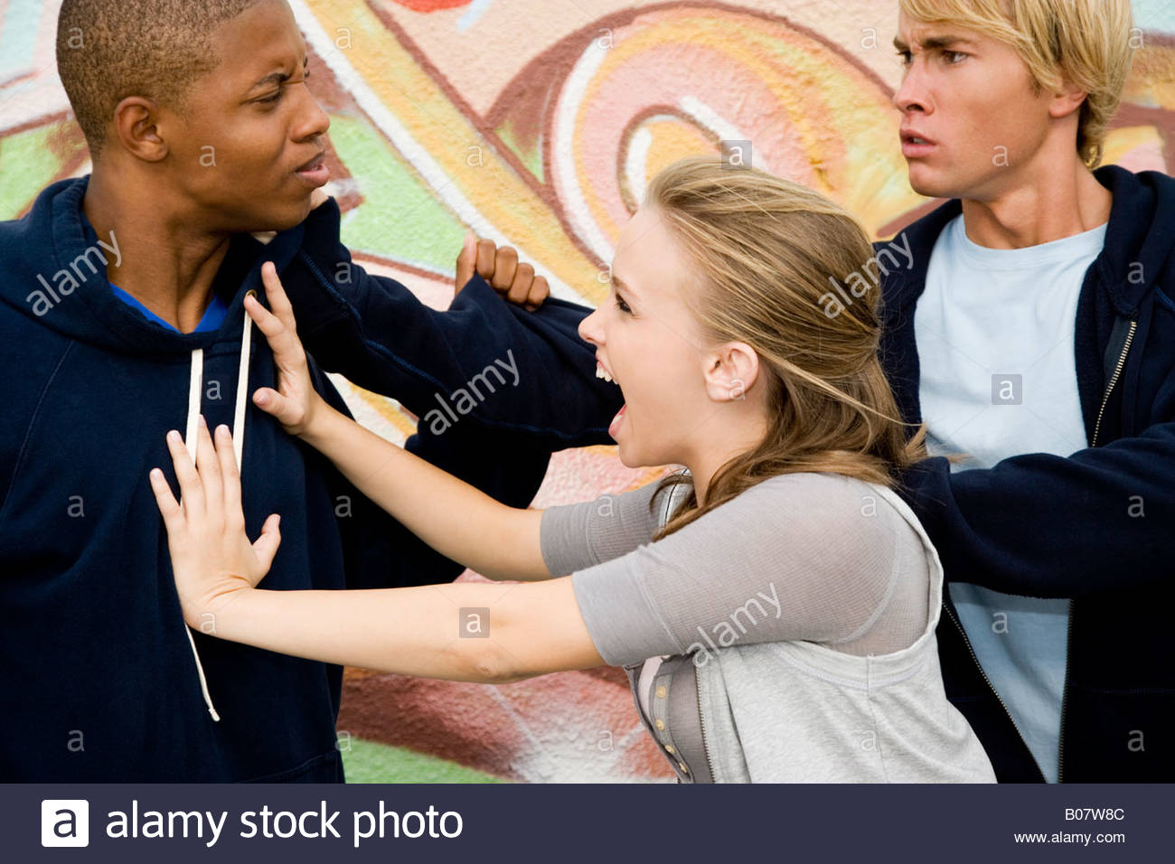 Two men fighting over a girl in front of a graffiti covered wall - Stock Image