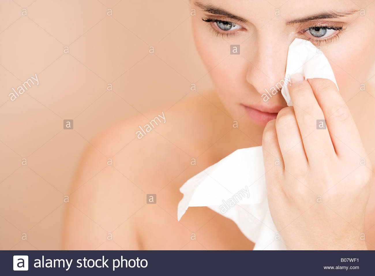 Woman crying, wiping tears away with a tissue - Stock Image