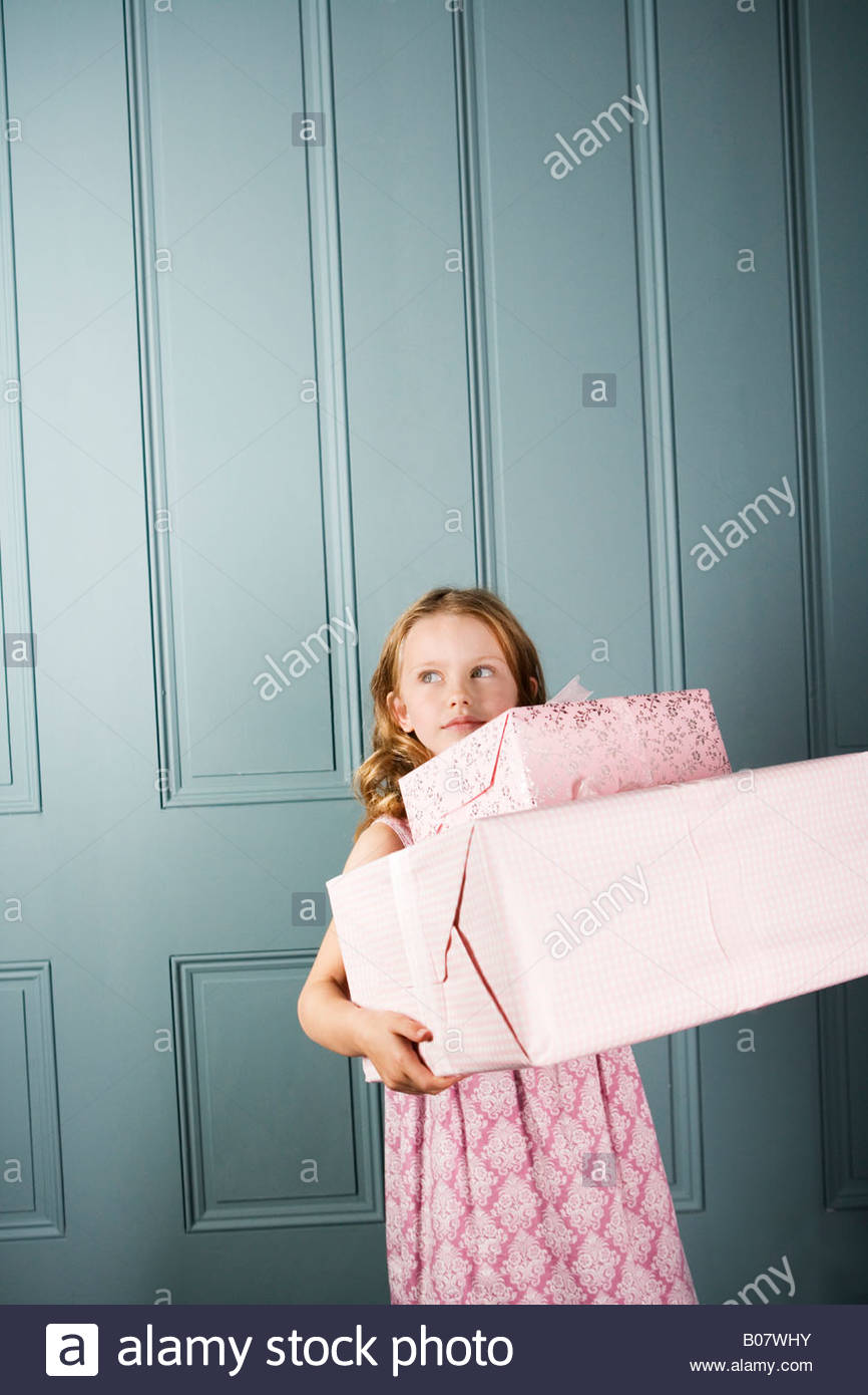 little girl carrying presents - Stock Image