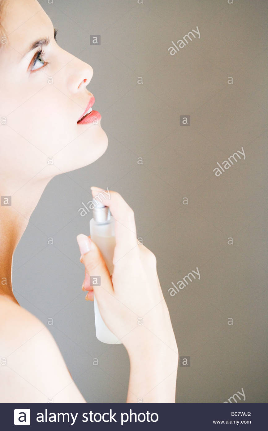 Young woman spraying perfume on her neck - Stock Image