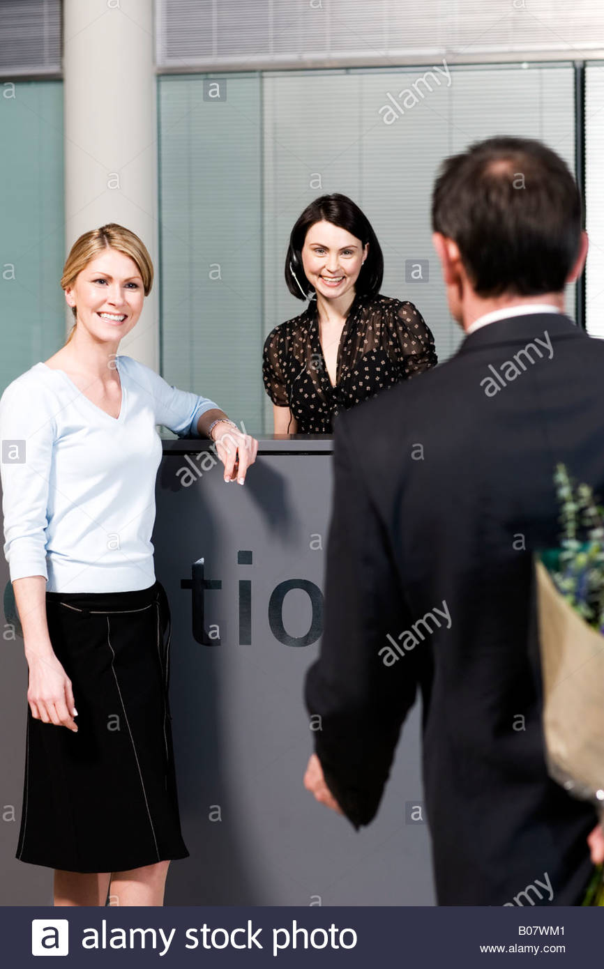 Businessman with bouquet of flowers being greeted by two women at office reception - Stock Image