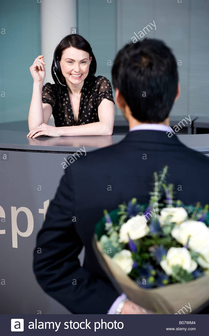 Businessman with bouquet of flowers being greeted by office receptionist - Stock Image